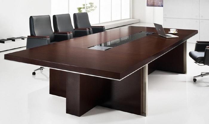 duży stół konferencyjny z prostokątnym blatem i szybą w jego centralnej części